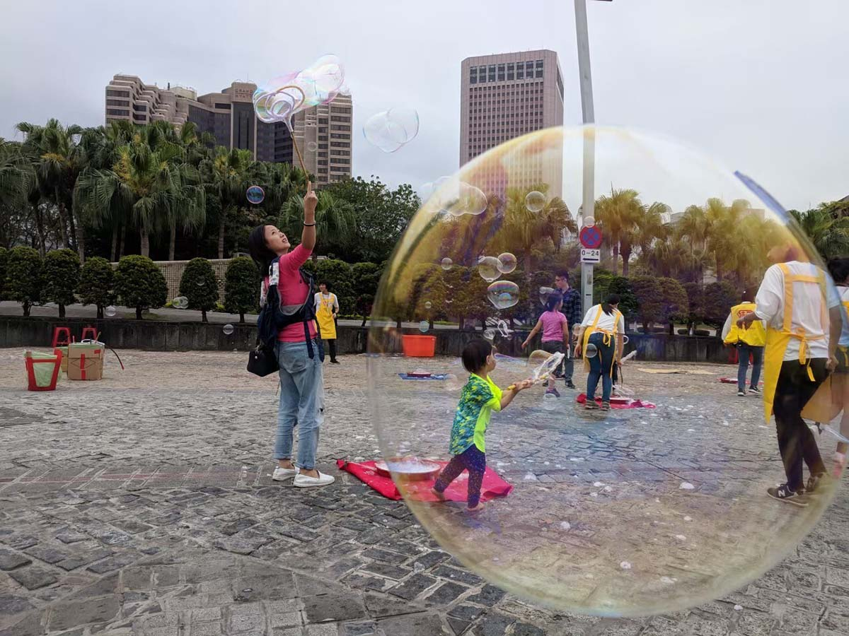 A photograph of a woman in Taiwan making soap bubbles in a public square with children playing along. A soap bubble is in the foreground, with the action in the background.