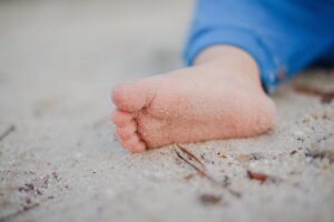 Photo of a baby foot on a beach, with a little of sand on sole of the foot
