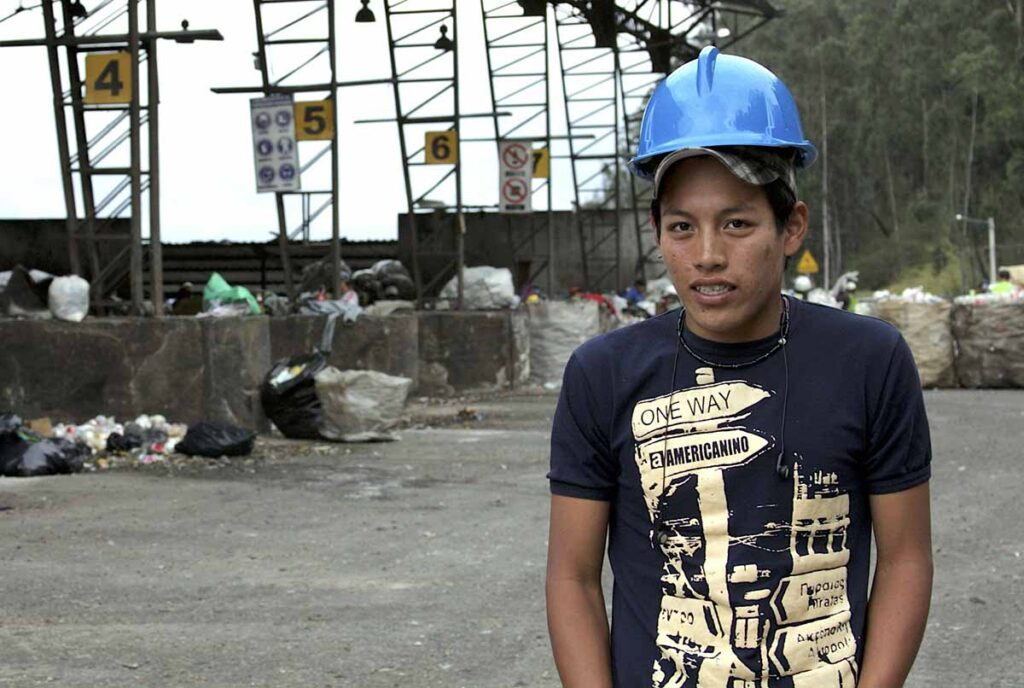 An image of a teenager, Marco, on the foreground, wearing a dark blue T-shirt, a cap and a helmet. In the background there is rubbish arranged in rows.