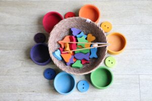 Round assorted-colors plastic cases. In the center one there are several wooden colorful figurines, shaped like fish, hearts and stars.