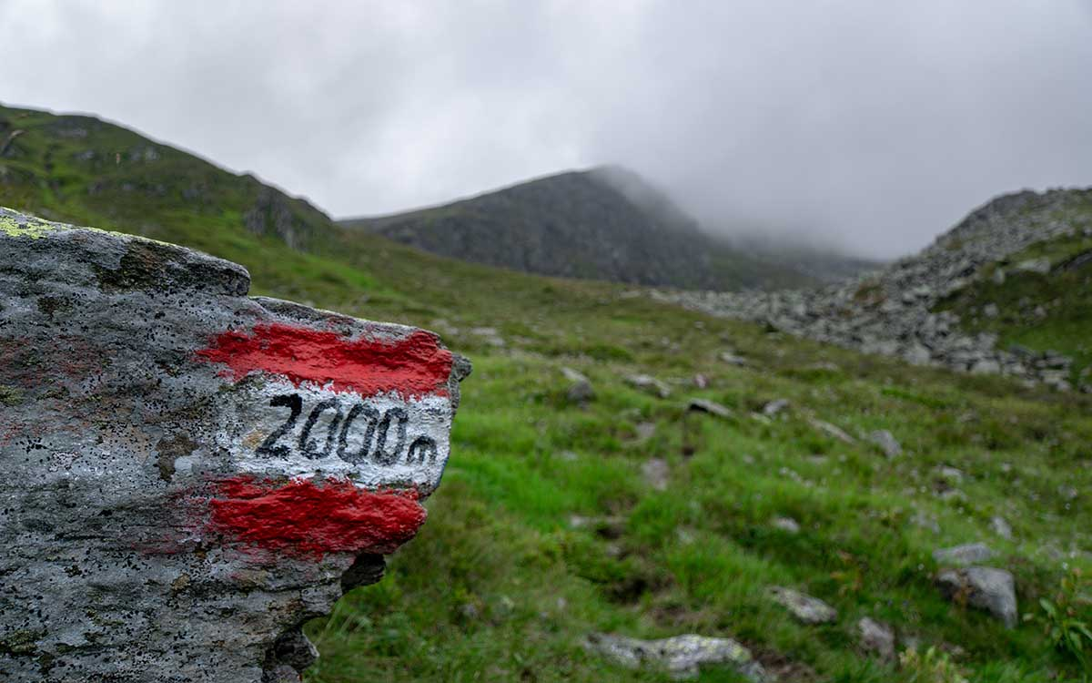 """red and white """"2000m"""" milestone on a foggy mountain"""