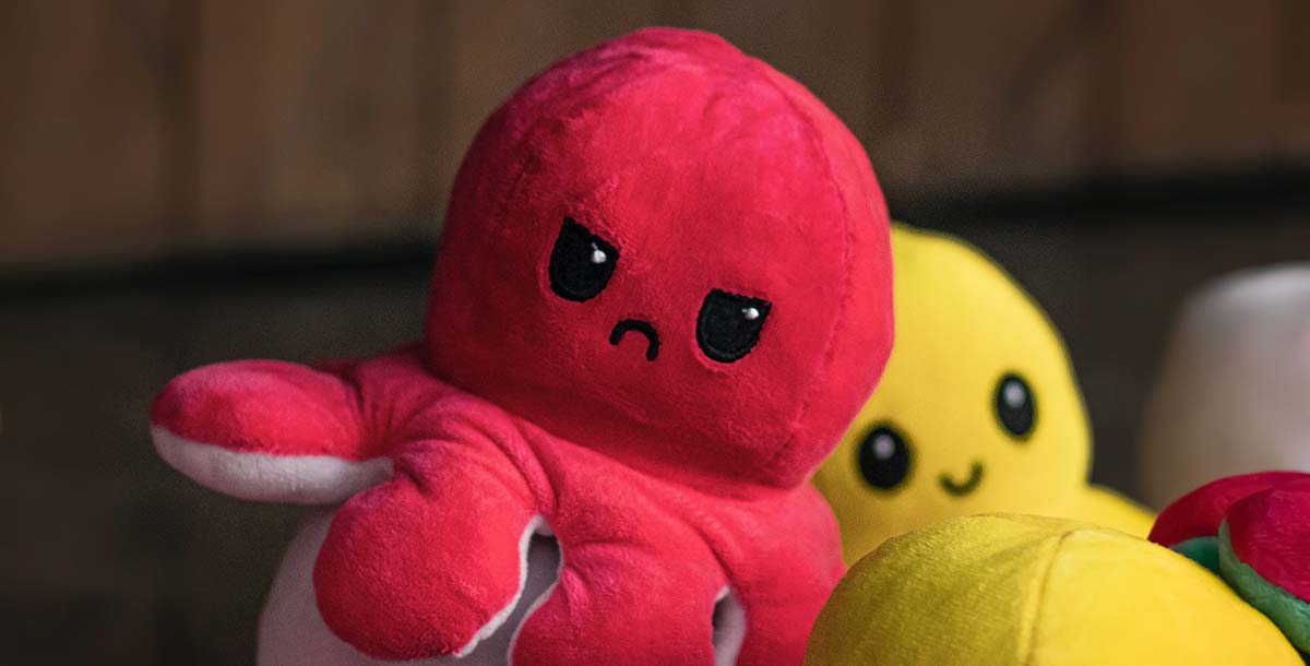 Red and yellow octopus plushes. The red one has an angry expression while the yellow one has an happy expression.