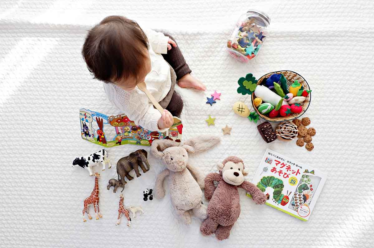 Child sitting on white cloth surrounded by toys.