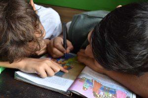boys writing on book