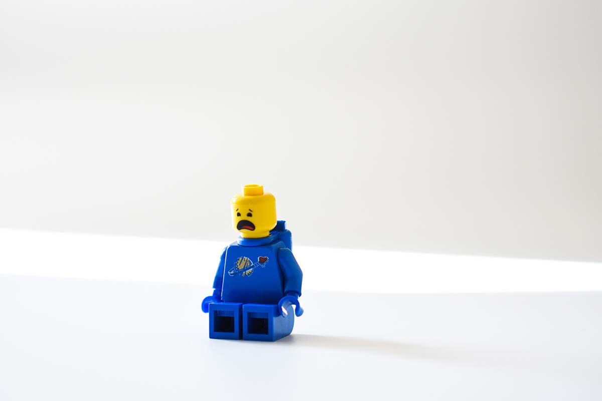 blue lego minifig on a white surface
